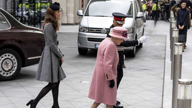 Kate walks behind the Queen as they arrive at the university