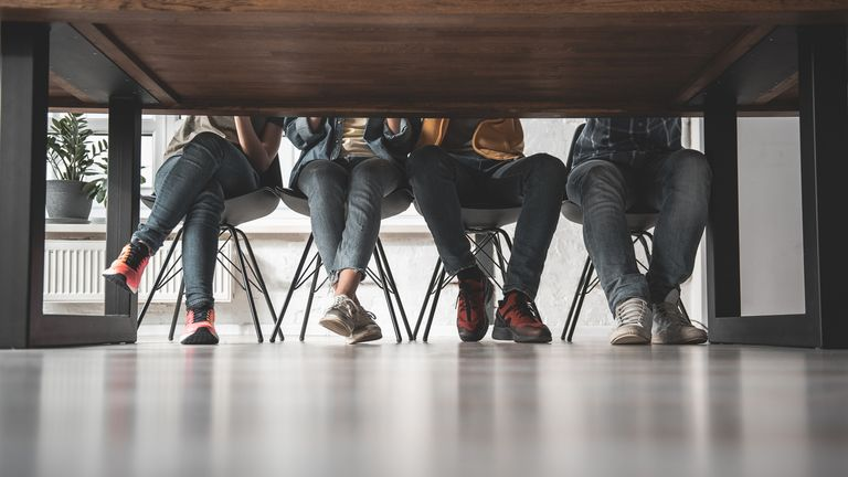 Lower body of young people sitting at the table. They are wearing casual clothes and sport shoes. Low angle. Copy space (Lower body of young people sitting at the table. They are wearing casual clothes and sport shoes. Low angle. Copy space, ASCII, 12