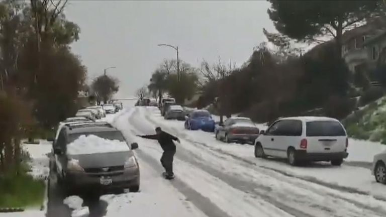 A snowboarder makes the most of a wild hailstorm that covered a Californian street in a thick layer of hailstones
