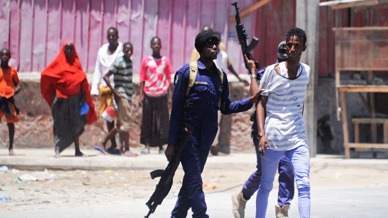 Somali soldiers arrest a civilian close to the scene of two explosions