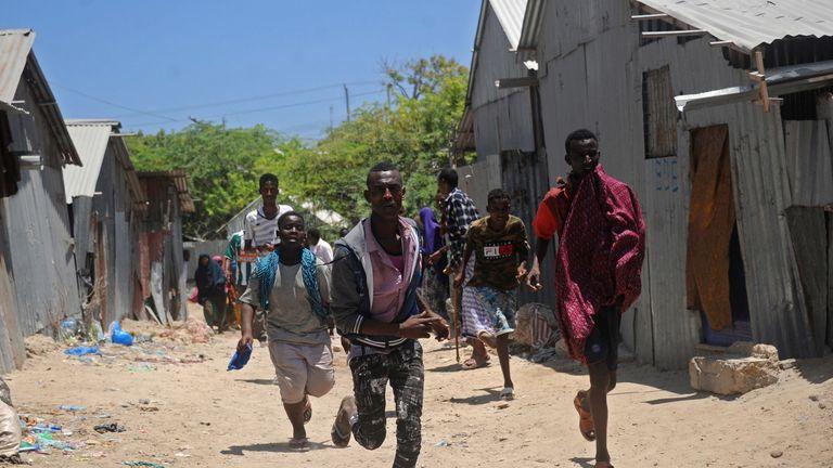 Civilians run from the scene