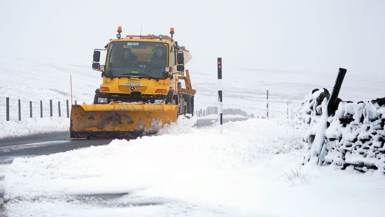 A gritter clears the road on the border between Cumbria and Northumberland following Storm Freya