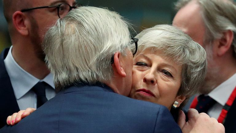 European Commission President Jean-Claude Juncker embraces with Prime Minister Theresa May at the EU summit in Brussels