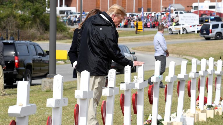 Donald and Melania Trump visit a row of 23 crosses for the victims of a tornado in Beauregard, Alabama