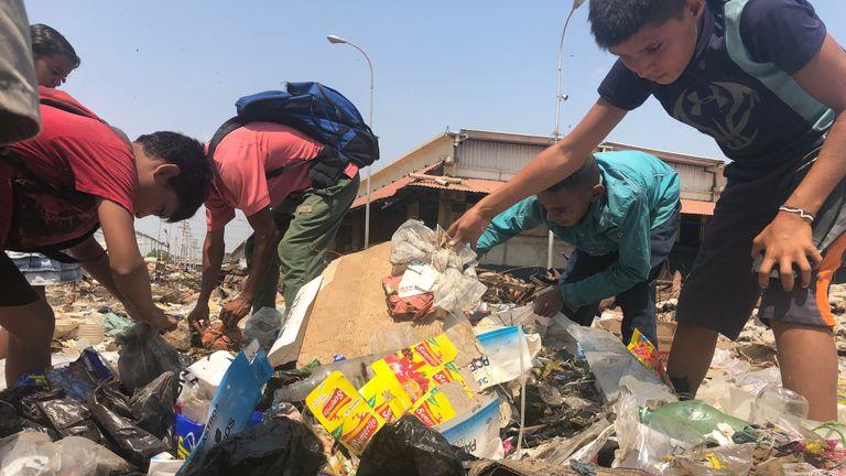 Los niños se meten en la basura por la comida.