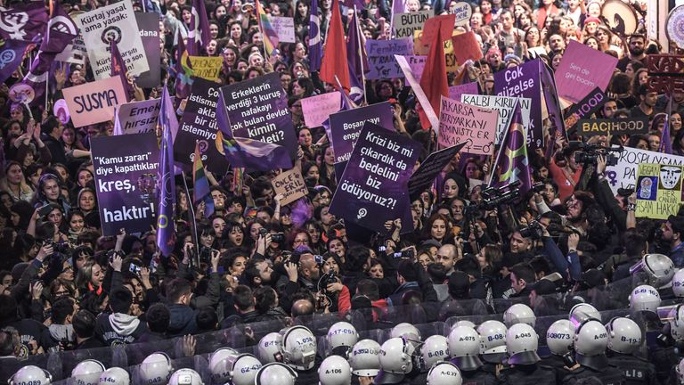 A placard reads 'We are in rebellion for freedom' while women shout slogans as Turkish anti-riot police officers try to push them back during a rally marking International Women's Day on Istiklal avenue in Istanbul on March 8, 2019