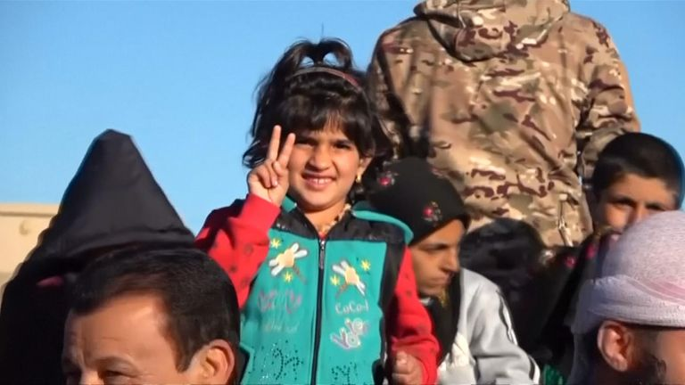 A Yazidi girl flashes a V-sign after arriving back in the Sinjar area after fleeing from Islamic State