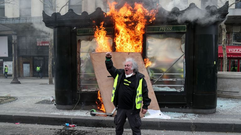 A protester in front of a burning kiosk