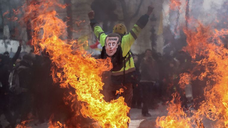 A man wearing a joke Emmanuel Macron mask on his back takes part in the protests