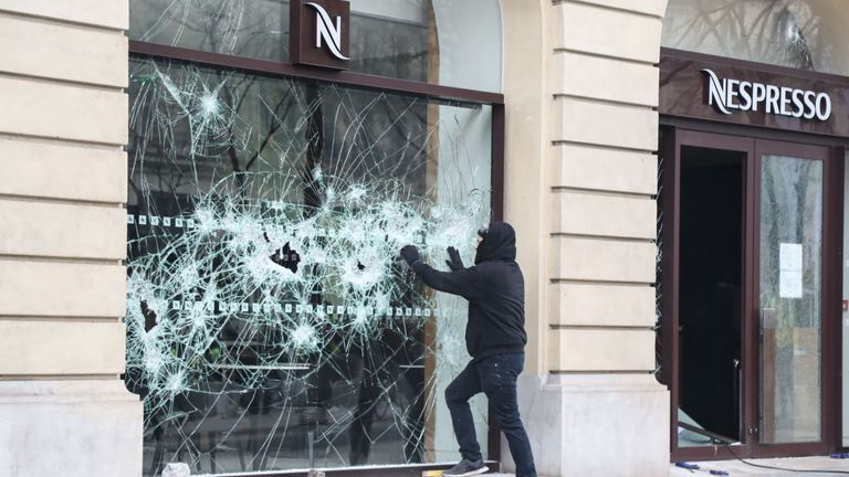 The window of a Nespresso store is smashed