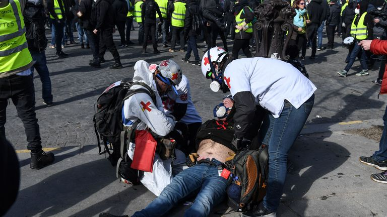 An injured protester receives treatment as he lies on the ground injured