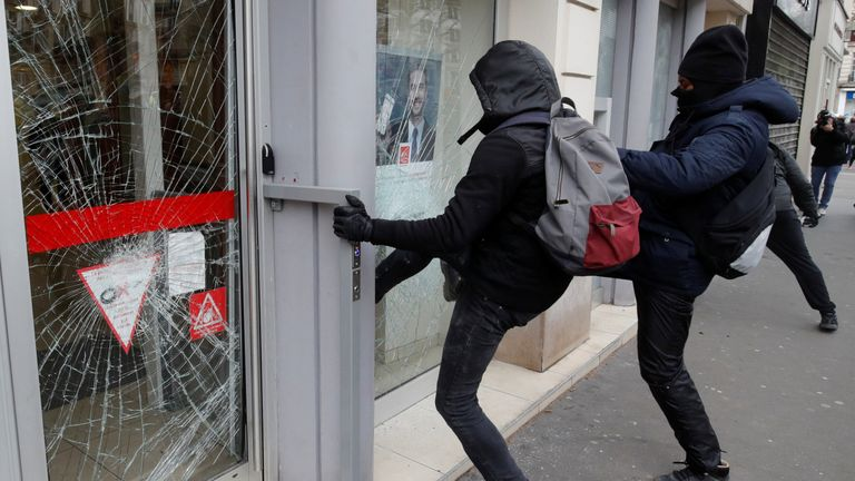 Protesters smash down the outside of a bank