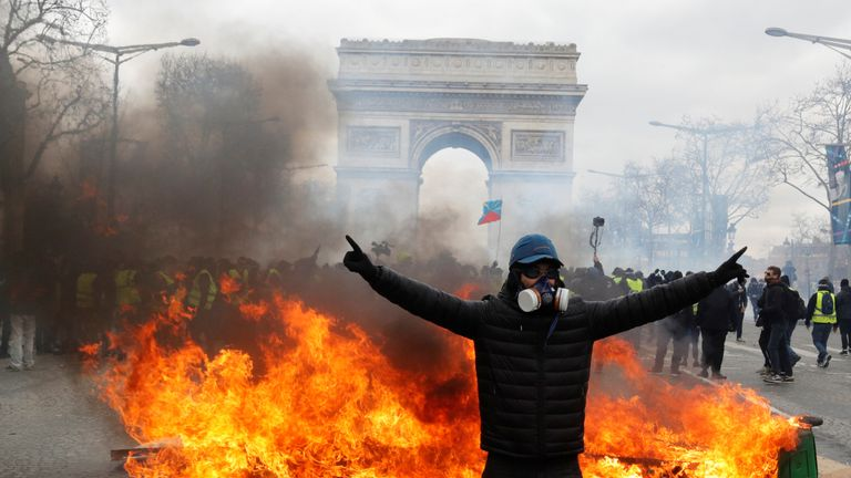 A protester stands in front of a burning barricade on the Champs-Elysees