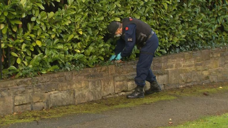 An officer searches a hedge near to where Yousef was killed