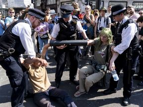 Police try to move climate activists who have glued their hands to a pipe in Oxford Circus