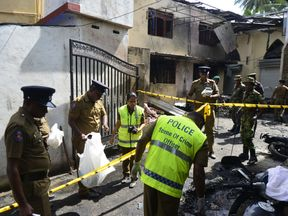 Sri Lankan security personnel and police investigators look through debris outside Zion Church following an explosion in Batticaloa in eastern Sri Lanka on April 21, 2019