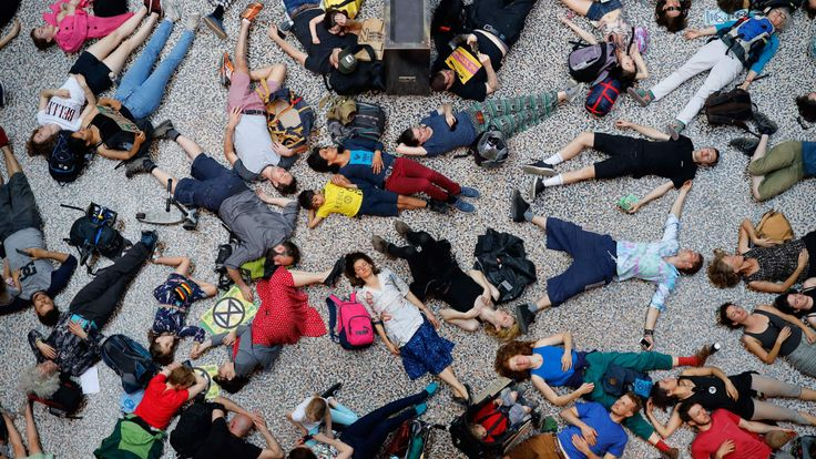 Climate change activists lie on the floor of the Natural History Museum