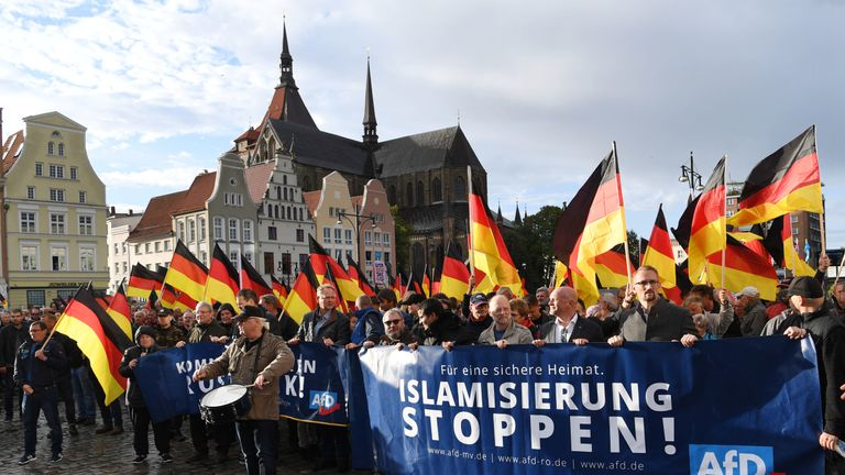 People carry German flags and a banner which reads 'Stop Islamization' during a march organised by the right-wing populist AfD in Rostock, north-eastern Germany on September 22, 2018. (Photo by Ralf Hirschberger / dpa / AFP) / Germany OUT (Photo credit should read RALF HIRSCHBERGER/AFP/Getty Images)