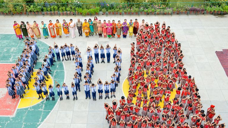 Indian school students and teachers stand in the shape of the number '100' on Friday
