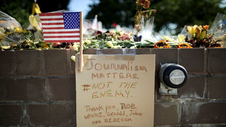 Flowers and hand-written notes at a makeshift memorial in Annapolis for the five employees killed by a gunman in June