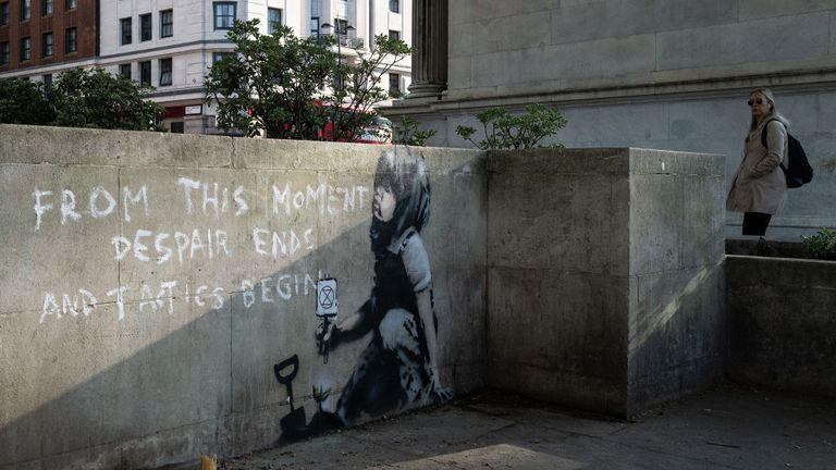 A commuter takes a double look at the suspected Banksy artwork