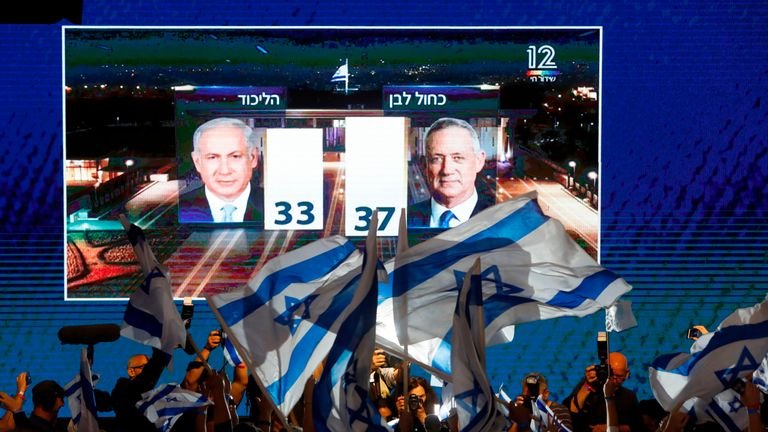 Supporters of the Blue and White alliance wave flags as exit polls emerge