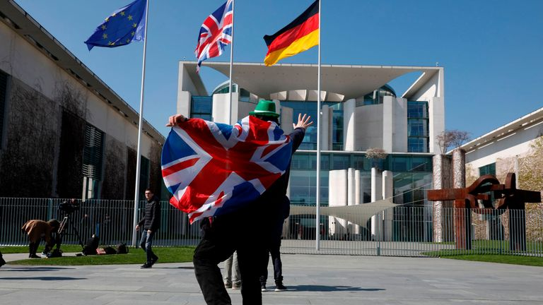 A man protests outside the German Chancellery as May meets Merkel
