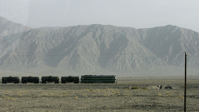 A train passes on tracks on the edge of the Tarim Basin on China's Silk Road to the West