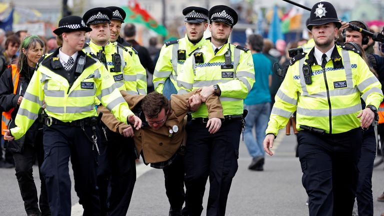Police officers detain a climate change activist at Waterloo Bridge during the Extinction Rebellion protest in London