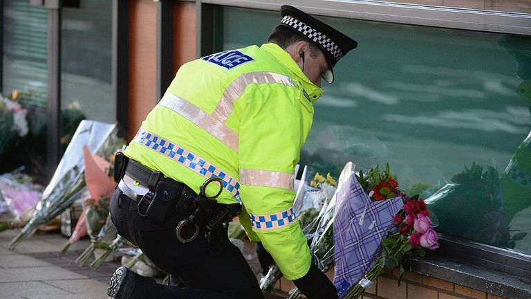 GLASGOW, SCOTLAND - DECEMBER 01: A police officer lays flowers near to The Clutha bar in Stockwell Street where a police helicopter crashed on the banks of the River Clyde on Friday night on December 01, 2013 in Glasgow, Scotland, United Kingdom. The crash which happened at 22:25 on Friday November 29, has claimed eight lives so far including that of Gary Arthur, 48, who is the first to be named, as well many injuries as a direct result of the accident. (Photo by Jeff J Mitchell/Getty Images)