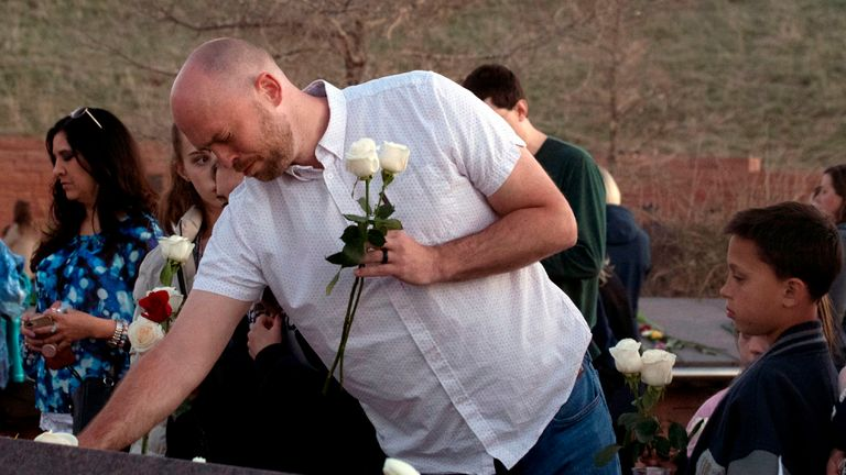 Will Beck, a Columbine High School massacre survivor, reacts while placing flowers at the Columbine Memorial at Clement Park in Littleton, Colorado, during a community vigil for the 20th anniversary of the Columbine High School mass shooting on April 19, 2019. - 12 students and one teacher were massacred by two heavily armed students nearly 20 years ago during the Columbine High School shooting on April 20, 1999. (Photo by Jason Connolly / AFP) (Photo credit should read JASON CONNOLLY/AFP/Getty