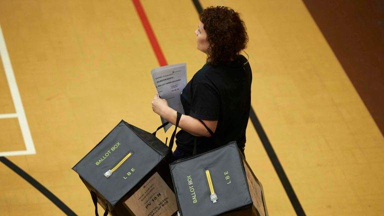 A staff member carries ballot boxes at a counting centre in Islington, London, on June 8, 2017, after the polls closed in Britain's general election. Prime Minister Theresa May is poised to win Britain's snap election but lose her parliamentary majority, a shock exit poll suggested on June 8, in what would be a major blow for her leadership as Brexit talks loom.