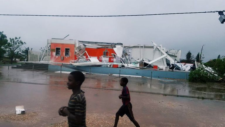 Children walk past a damaged building after Cyclone Kenneth hit Pemba