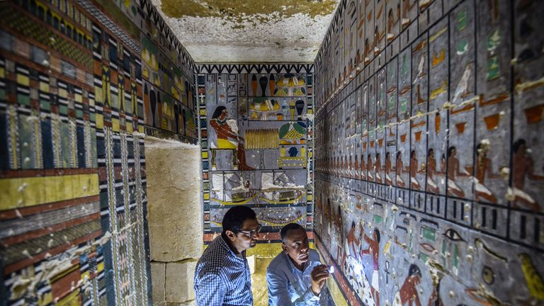 Experts examine markings on the wall of the tomb near Saqqara