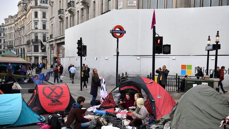 Activists sit with their tents in the road after sleeping at Oxford Circus on the second day of an environmental protest by the Extinction Rebellion group, in London on April 16, 2019.