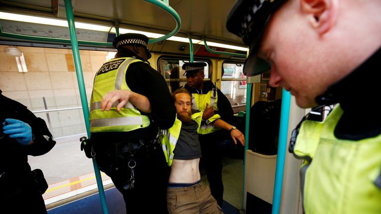 Police detain a protester as climate change activists demonstrate during the Extinction Rebellion protest, at Canary Wharf DLR station in London, Britain April 17, 2019. REUTERS/Henry Nicholls