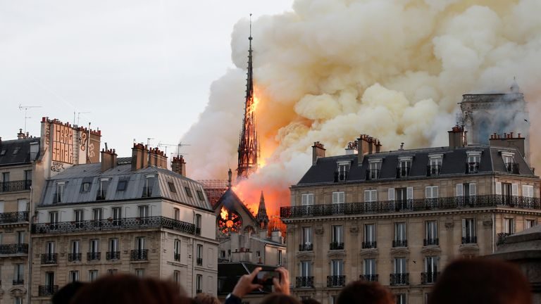 Onlookers gasp in shock as the spire atop Notre-Dame cathedral collapses in fire.