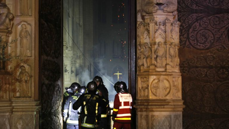 Firefighters at the entrance of the Notre-Dame as they work to put out the blaze