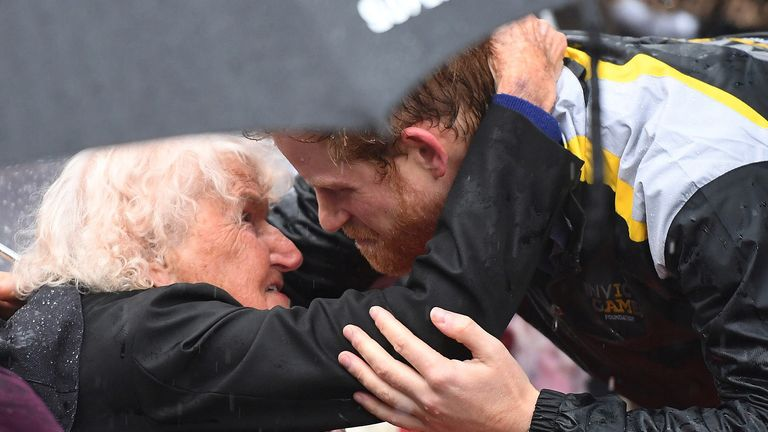 Britain's Prince Harry hugs Daphne Dunne, 97, during a walk around The Rocks district in rainy Sydney, Australia, June 7, 2017, during his promotion of the 2018 Invictus Games. REUTERS/David Moir/Pool
