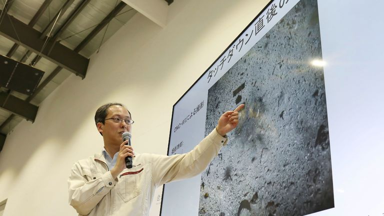 A Jaxa engineer points at an image of the Ryugu asteroid