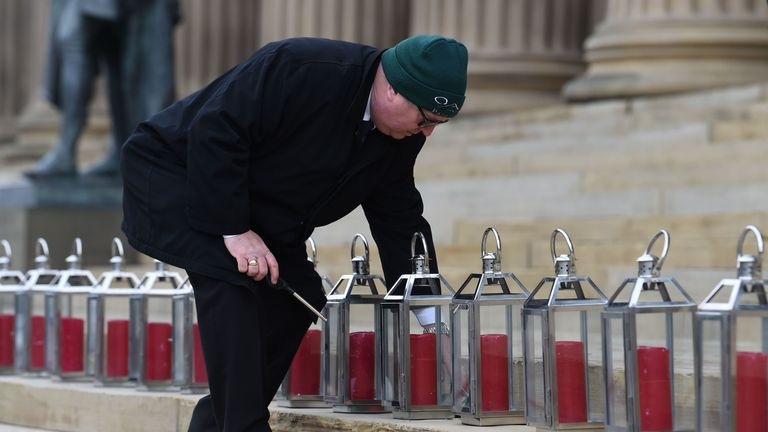 A man lights candles in 96 lanterns arranged on the steps of St Georges Hall in Liverpool, northwest England, on April 15, 2019 to commemorate the 30th anniversary of the Hillsborough football stadium disaster in which 96 Liverpool football fans were killed. - The northern city of Liverpool remembered the 96 victims of the fatal crush at an FA Cup football tie between Liverpool and Nottingham Forest at Sheffield's Hillsborough stadium on April 15, 1989, 30 years to the day.