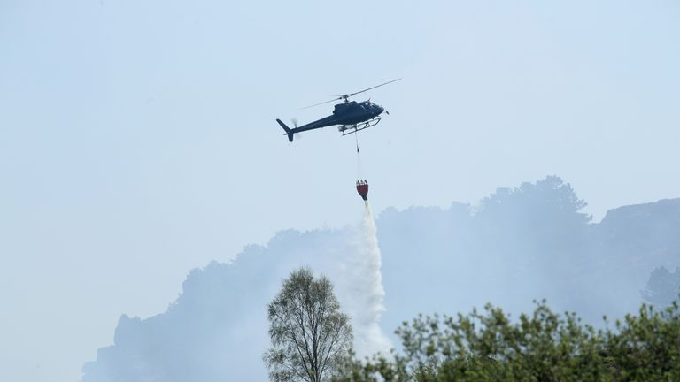 A helicopter is being used to dump water on the fire