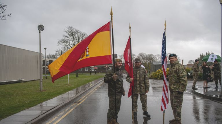 Spanish, Turkish and American NATO military personnel hold their nation's flags in driving rain during the NATO commemorative parade at Imjin Barracks on April 4, 2019 in Gloucester, England