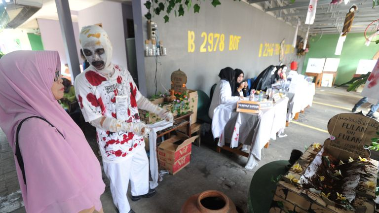 An Indonesian election worker dressed as a ghost welcomes voters in Jakarta