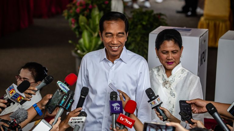 Indonesian President Joko Widodo and his wife Iriana speak to journalists after he cast his ballot