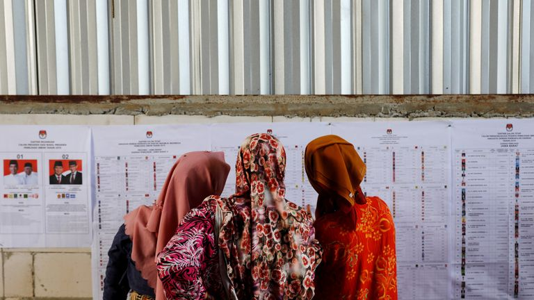 People look at voting information at a polling station during elections in Bogor, West Java