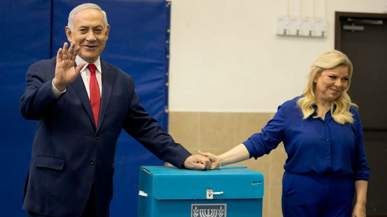 Israeli Prime Minister Benjamin Netanyahu (L) and wife Sara cast their ballot