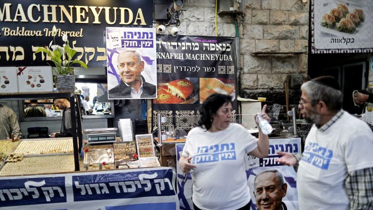 Supporters of Israeli Prime Minister Benjamin Netanyahu stand next to posters bearing his portrait at the Machane Yehuda market in Jerusalem on April 8, 2019, a day ahead of the electoral polls. - Israelis vote on April 9 in a high-stakes election on whether to extend Prime Minister Benjamin Netanyahu's long tenure in power despite corruption allegations against him and a strong challenge by an ex-military chief. (Photo by THOMAS COEX / AFP) (Photo credit should read THOMAS COEX/AFP/Getty Images