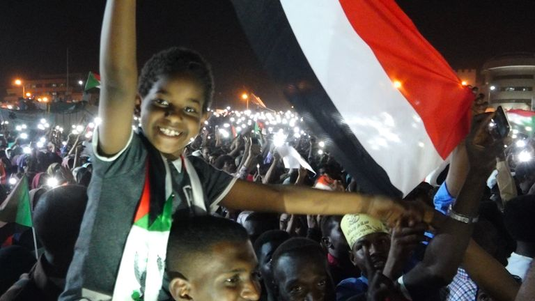 A child waves a flag at protests in the Sudanese capital of Khartoum