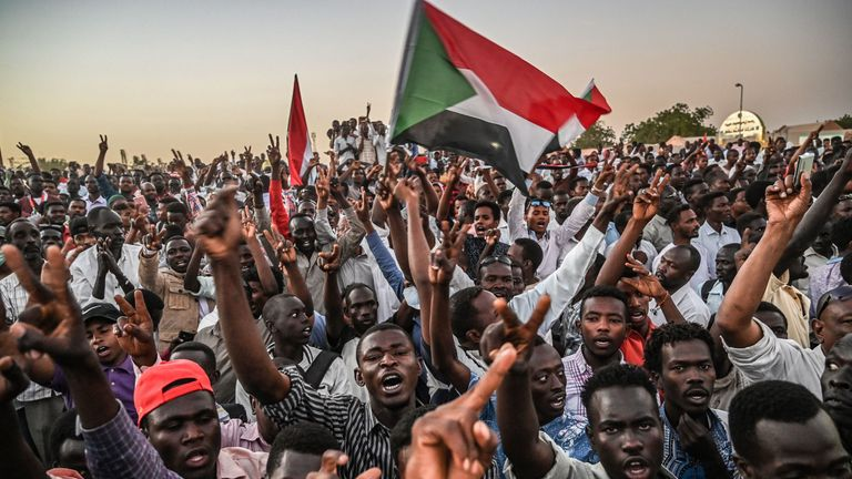 Sudanese protesters gather as they shout slogans and wave national flags during a protest outside the army headquarters in the capital Khartoum on April 21, 2019